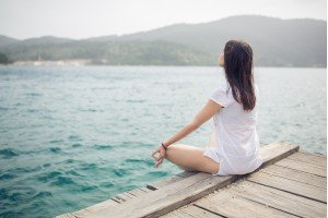 woman peacfully sitting near lake meditating