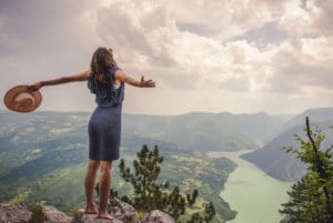 energy renewal a woman standing on mountain top with open arms