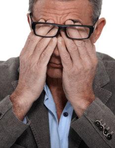 tired irritable man rubbing his eyes